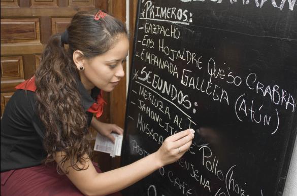 restaurant employee writing on chalkboard