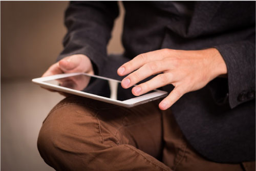 man using ipad sitting down