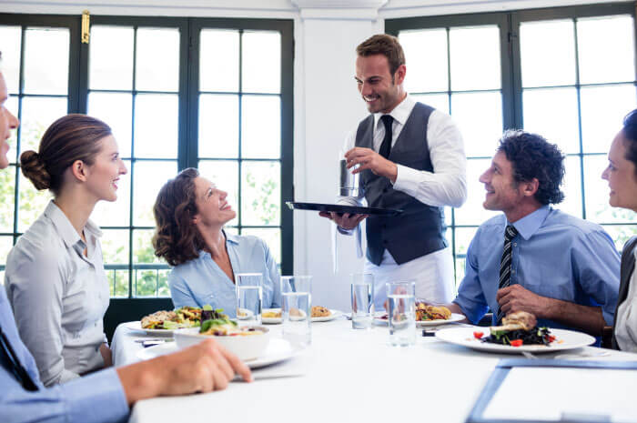 Waiter with customers performing table side service using iPad POS